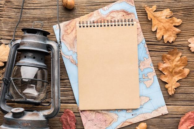 Draufsicht des notizbuchs mit karte und herbstlaub