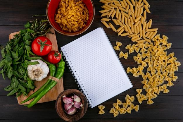 Draufsicht des notizbuchs mit rohen nudeltomaten knoblauch mit chili-pfeffer und minze auf einem schneidebrett auf einer holzoberfläche