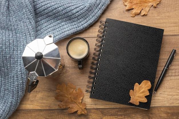 Draufsicht des notizbuchs mit tasse kaffee und wasserkocher