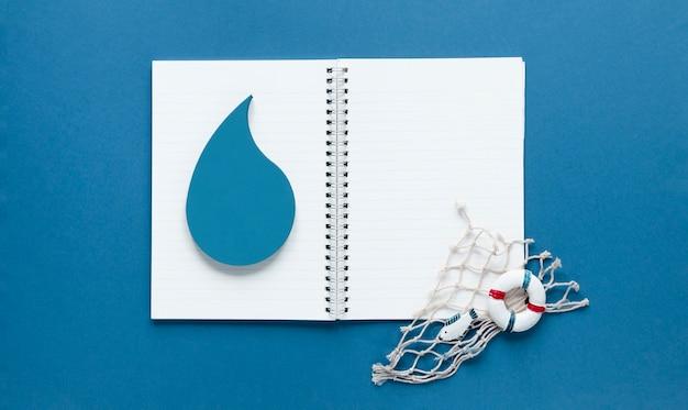 Draufsicht des notizbuchs mit wassertropfen und fischernetz