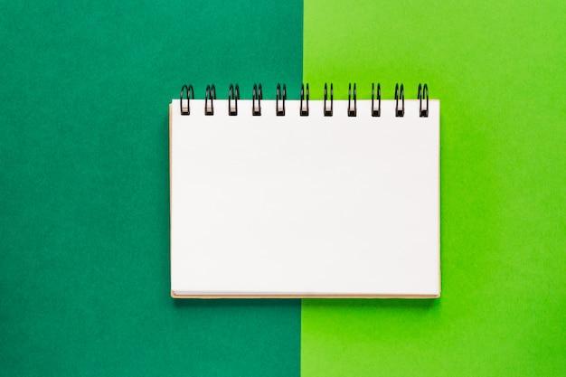 Draufsicht des offenen leeren gewundenen notizbuches auf grünem buntem hintergrund