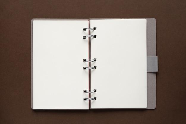 Draufsicht des offenen leeren notizbuches mit abdeckung vom recyclingpapier auf braunem hintergrund
