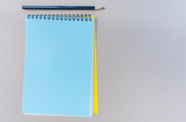 Draufsicht des offenen leeren notizbuchs der spirale mit bleistift auf brauner wand.