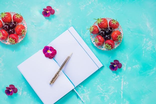 Draufsicht des offenen leeren notizbuchs, verspotten über blaue schreibtischwand. wildbeerenfrucht-arrangement. erdbeeren, konzept des geschäftigen morgenfrühstücks, sommer-listenplaner.