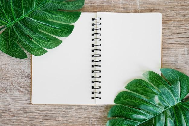 Draufsicht des offenen notizbuches des freien raumes auf hölzernem schreibtischhintergrund mit grünem tropischem monstera verlässt.