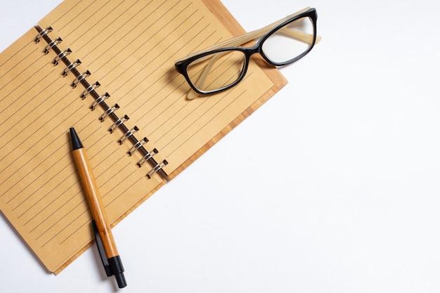 Draufsicht des offenen notizbuchs mit stift oder bleistift und gläsern lokalisiert auf weißem hintergrund