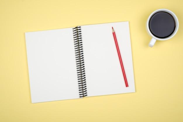 Draufsicht des offenen spiralblanknotizbuchs auf buntem schreibtisch