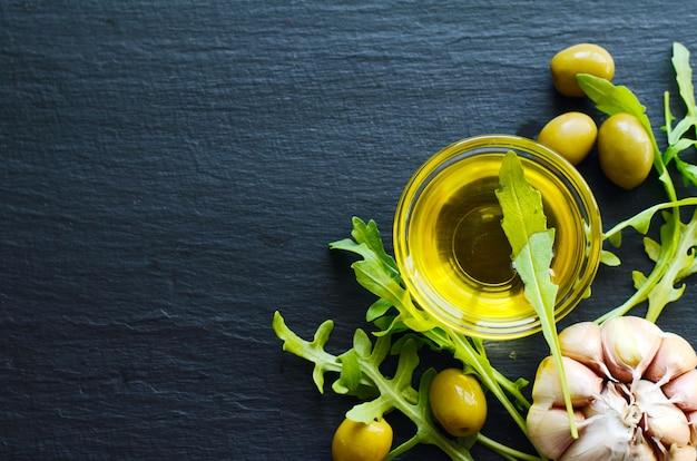 Draufsicht des olivenöls und der bestandteile - oliven, knoblauch und ruccola