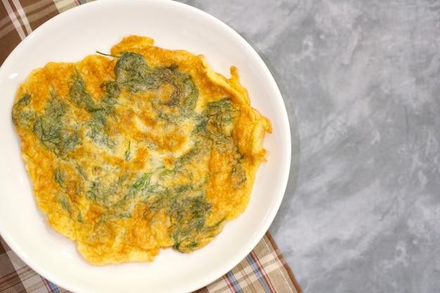 Draufsicht des omeletts (omelett) mit dill diente auf weißer platte