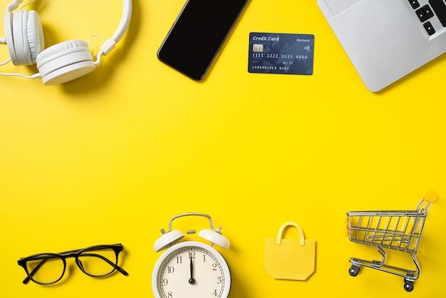 Draufsicht des online-shopping-konzepts mit kreditkarte, smartphone und computer einzeln auf gelbem tischhintergrund im büro.
