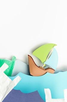 Draufsicht des papierboots auf wellen mit plastiktüten