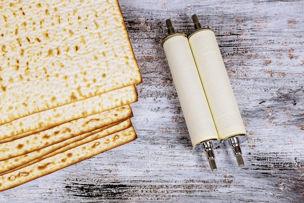 Draufsicht des passahfesthintergrundes. matzoh jüdisches feiertagsbrot und torahrolle während