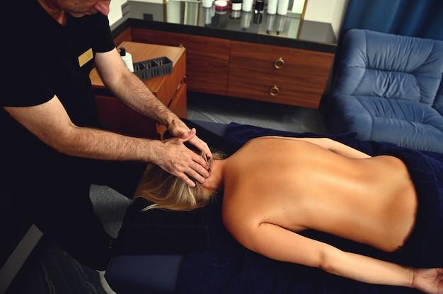 Draufsicht des physiotherapeuten, der einer frau, die auf einem massagetisch im wellnesscenter liegt, eine nackenmassage gibt. körperpflegekonzept