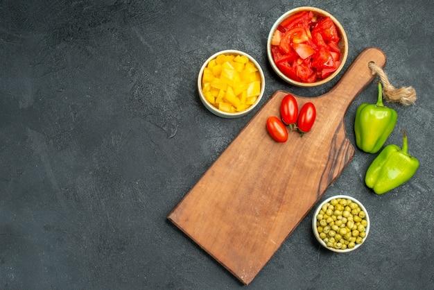 Draufsicht des plattenständers mit tomaten darauf und anderem gemüse auf der seite mit freiem platz für text auf dunkelgrauem hintergrund
