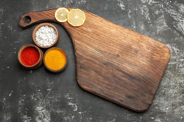 Draufsicht des plattenständers mit zitrone darauf und kräutern auf seite auf dunkelgrauem tisch