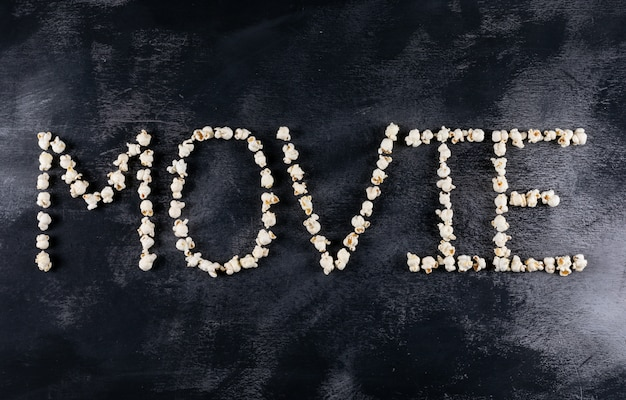 Draufsicht des popcornfilmwortes auf schwarzer horizontaler