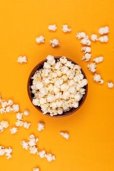 Draufsicht des popcorns in der schüssel auf gelber vertikal