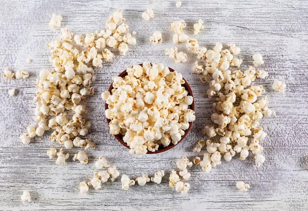 Draufsicht des popcorns in der schüssel auf weißer hölzerner horizontaler