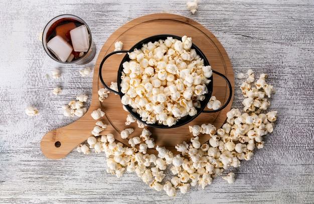 Draufsicht des popcorns in der schwarzen pfanne und im hölzernen schneidebrett mit limonade auf der weißen oberfläche horizontal