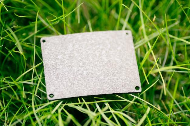 Draufsicht des quadratischen grauen lederpatchs für die kreative gestaltung von rasengrünem gras mit logo-tag.