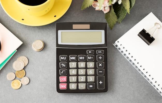 Draufsicht des rechners, des notizblocks, der tassen mit kaffee, der münzen und der grünen pflanze auf grauem tisch.