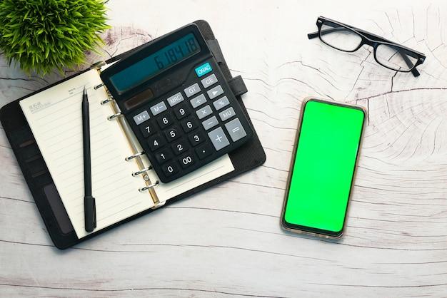 Draufsicht des rechners, des notizblocks und des smartphones auf tisch