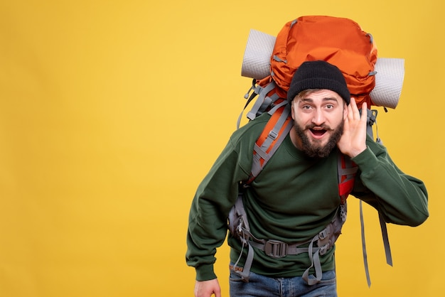 Draufsicht des reisekonzepts mit dem jungen mann mit packpack, der dem letzten klatschen zuhört
