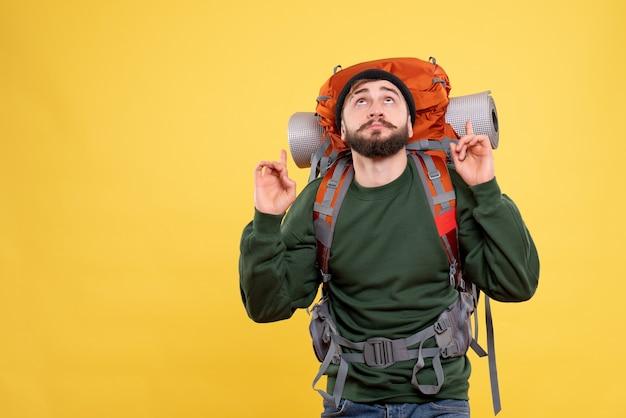 Draufsicht des reisekonzepts mit dem jungen mann mit packpack und nach oben zeigend