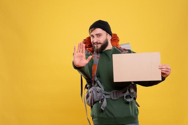 Draufsicht des reisekonzepts mit dem selbstbewussten jungen mann mit packpack und freiem platz zum schreiben, der fünf zeigt