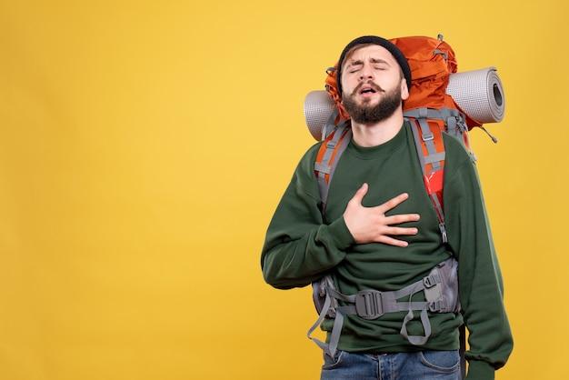 Draufsicht des reisekonzepts mit dem unruhigen jungen mann mit dem packpack, der unter herzinfarkt leidet