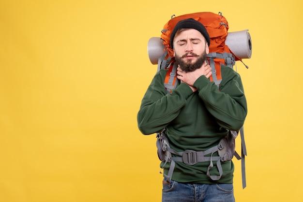 Draufsicht des reisekonzepts mit dem unruhigen jungen mann mit packpack, der unter halsschmerzen leidet