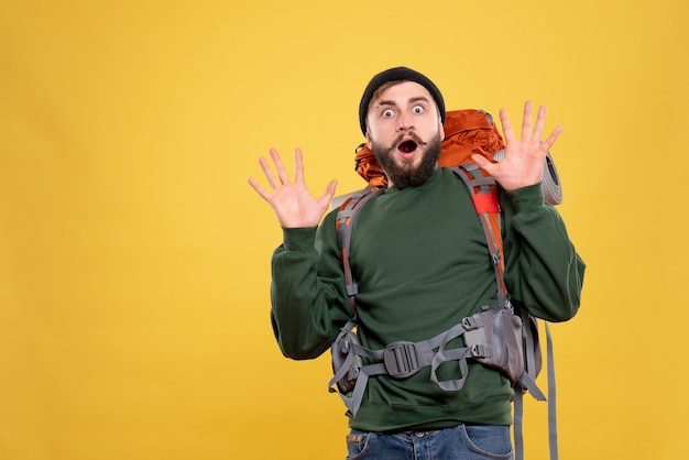 Draufsicht des reisekonzepts mit dem verängstigten emotionalen jungen mann mit packpack