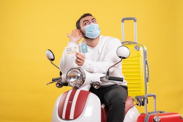 Draufsicht des reisekonzepts mit einem jungen mann in medizinischer maske, der auf einem motorrad mit gelbem koffer darauf sitzt und ein ticket hält, das dem letzten klatsch lauscht