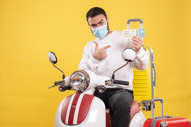 Draufsicht des reisekonzepts mit jungem ehrgeizigem kerl in medizinischer maske, der auf dem motorrad sitzt