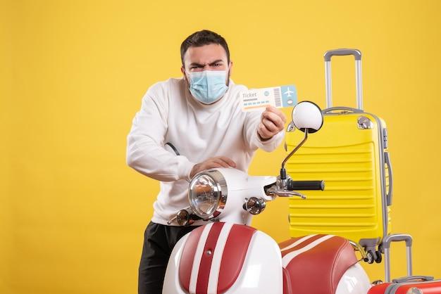 Draufsicht des reisekonzepts mit jungem mann in medizinischer maske, der in der nähe des motorrads steht