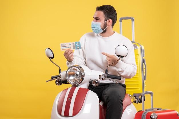 Draufsicht des reisekonzepts mit jungem zögerndem mann in medizinischer maske, der auf dem motorrad sitzt sitting
