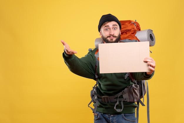 Draufsicht des reisekonzepts mit neugierigem jungem kerl mit packpack, der freien raum zum schreiben hält