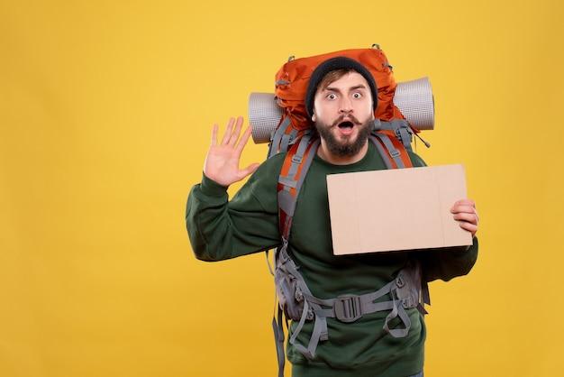 Draufsicht des reisekonzepts mit schockiertem jungen mann mit packpack und freiem platz zum schreiben, der fünf zeigt