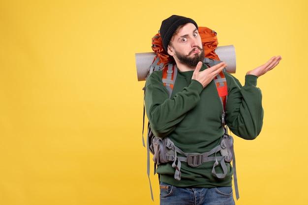 Draufsicht des reisekonzepts mit wunderndem jungem kerl mit packpack