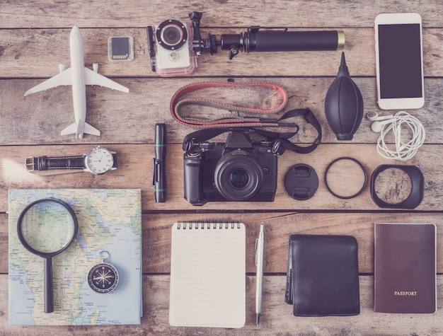 Draufsicht des reisekonzepts und des arbeitsraumfotografen mit digitalkamera, aktionskamera, speicherkarten-aufbewahrungsbox, notizbuch und kamerazubehör auf hölzernem hintergrund