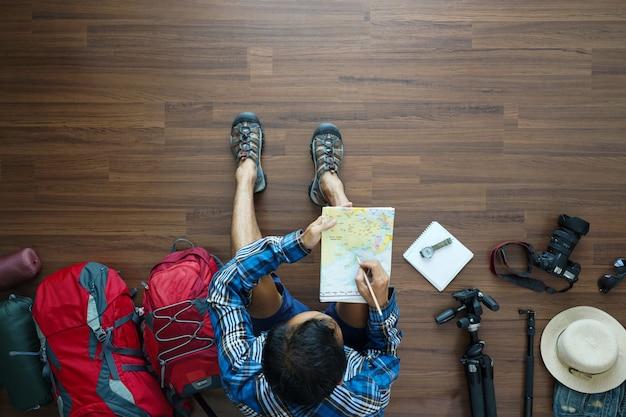 Draufsicht des reisenden mann plan mit karte halten