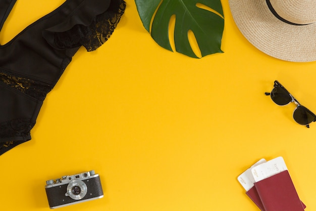 Draufsicht des reisendzubehörs, des badeanzugs, des hutes, der gläser, der kamera, der pässe und der flugtickets, des tropischen palmblattes auf gelbem sommerhintergrund mit kopienraum für text. reiseferienkonzept. flach liegen