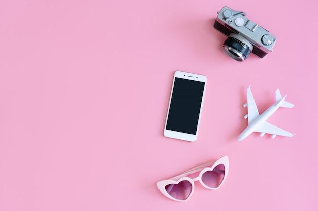 Draufsicht des reisezubehörs auf rosa hintergrund, reisekonzept. flache lage, kopierraum