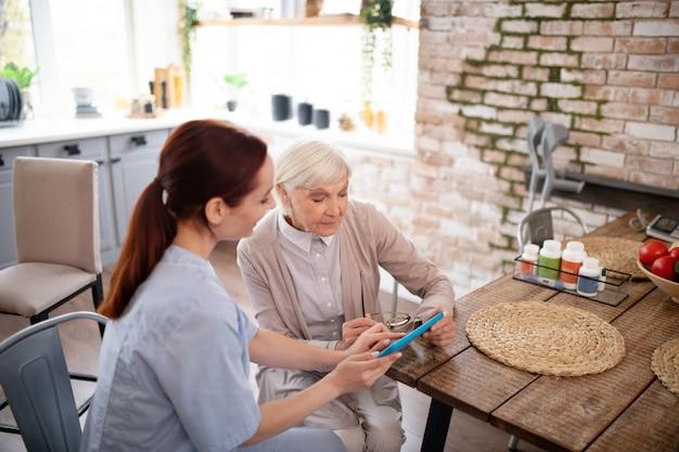 Draufsicht des rentners mit tablette mit hilfe der pflegekraft