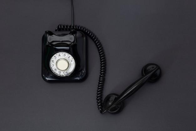 Draufsicht des retro-telefons der 1960er jahre lokalisiert auf einem schwarzen hintergrund. platz für text. kommunikationskonzept.