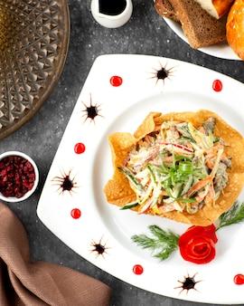 Draufsicht des rindfleischsalats mit gemüse und mayonnaise in der fladenbrotkruste
