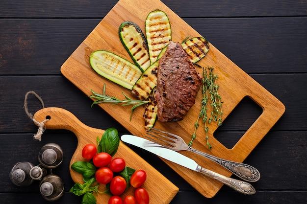 Draufsicht des rindfleischsteaks und der zucchini diente mit frischer tomatenkirsche und basilikum auf hölzernem schneidebrett