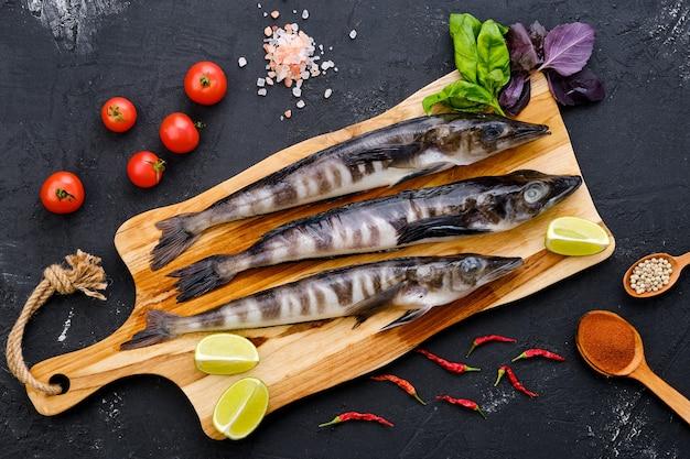Draufsicht des rohen frischen eisfischs auf hölzernem schneidebrett mit gewürzen und kräutern
