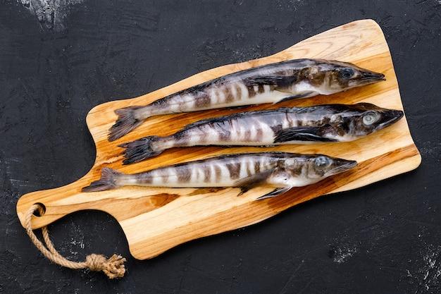 Draufsicht des rohen frischen eisfischs auf hölzernem schneidebrett