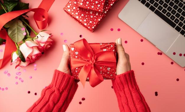 Draufsicht des rosa desktops mit blumen und geschenkboxen